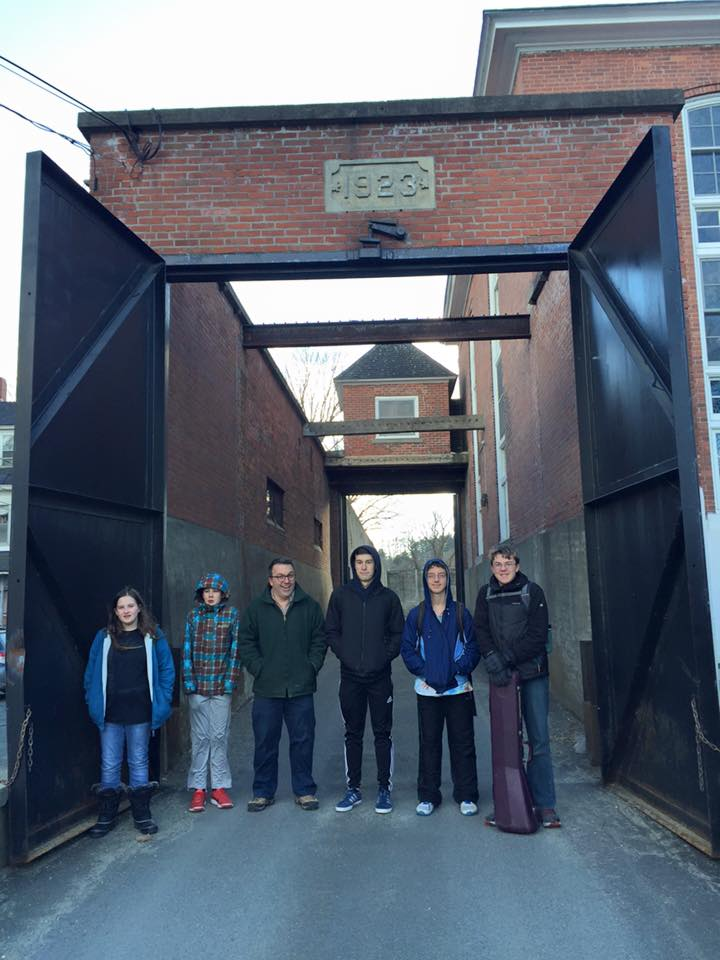 Tour of former prison and team photo next to gate damaged during prisoner escape in 1950s.